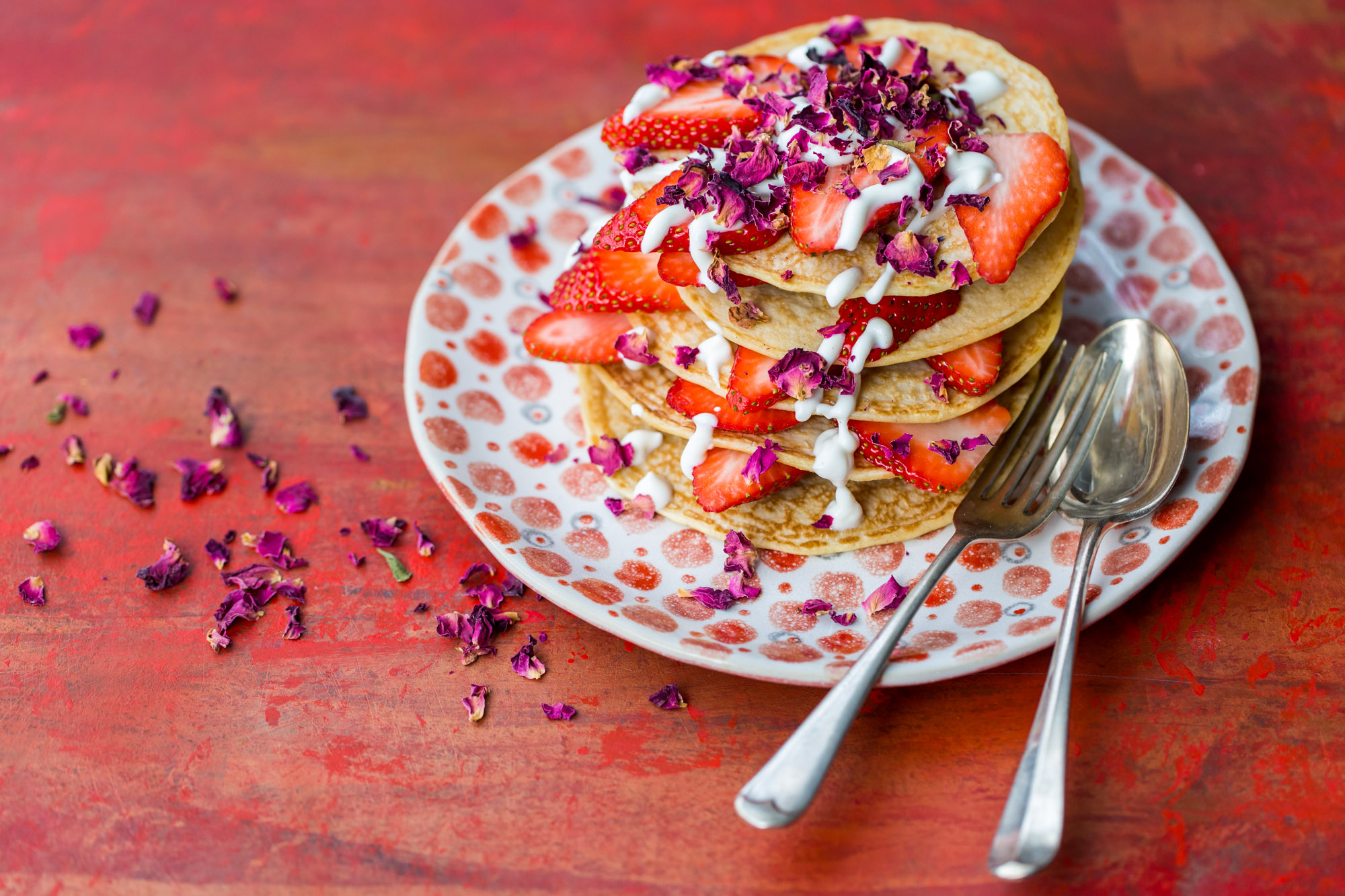 Pancakes with strawberries and cream - red rose petals