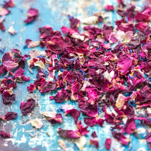 Scattering of dried wedding confetti, small red & pale pink rose petals, blue cornflower and scented lavender.