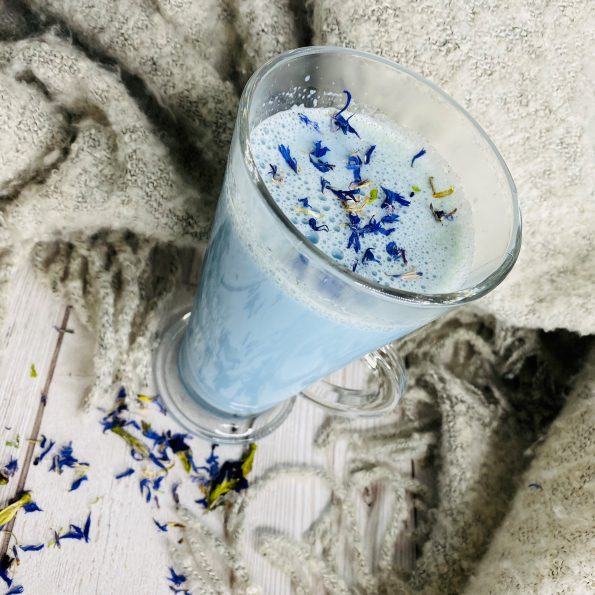 Blue milk in tall latte glass with blue cornflower scattered around.